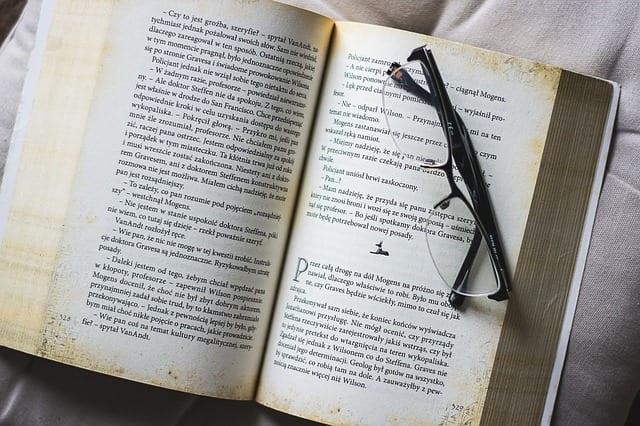 libro abierto y unas gafas sobre el. Actividades para ancianos. Lectura de Libros