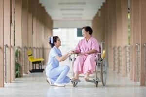 Enfermera titulada asistiendo a una persona de la tercera edad en silla de ruedas
