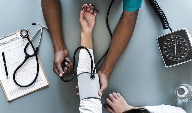 imagen de un doctor tomando la tensión a una mujer. Cuidados post hospitalarios