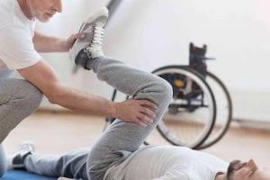 fisioterapeuta realizando ejercicios de rehabilitación a un paciente con parálisis