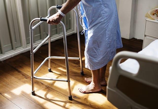 anciano apoyándose en un andador. Fisioterapia en tu casa tras sufrir un accidente