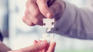 manos sujetando piezas de puzzle. Hacer puzzles es bueno para mejorar el estado mental de las personas mayores.