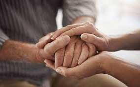 manos de un cuidador joven sosteniendo las manos de un anciano.