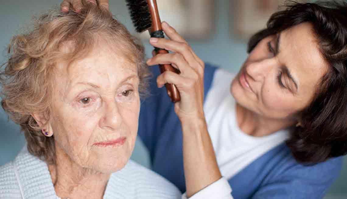 mujer peinando a su madre anciana.