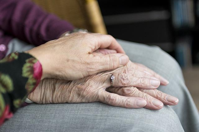 manos de cuidador sobre manos de un anciano. Evaluación de las necesidades de atención.