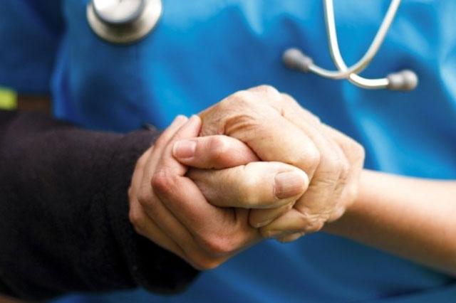Enfermera sosteniendo la mano de una anciano. Las enfermeras son el nexo entre el cuidador y el paciente mayor.