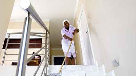 Trabajadora limpiando una escalera. Características de las trabajadoras domésticas.