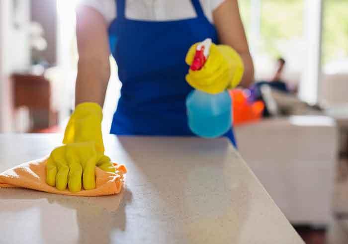 empleada del hogar limpiando una mesa.